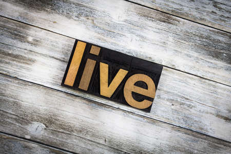 typescript: The word live written in wooden letterpress type on a white washed old wooden boards background. Stock Photo