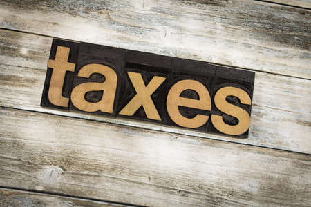The word taxes written in wooden letterpress type on a white washed old wooden boards background. Stock Photo