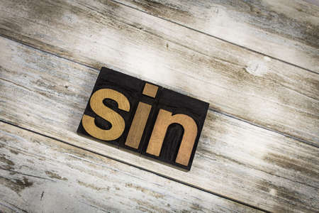 The word Sin written in wooden letterpress type on a white washed old wooden boards background.
