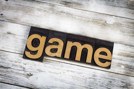 letterpress words: The word game written in wooden letterpress type on a white washed old wooden boards background. Stock Photo