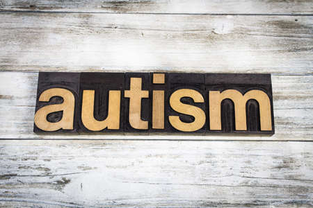 developmental disorder: The word autism written in wooden letterpress type on a white washed old wooden boards background. Stock Photo