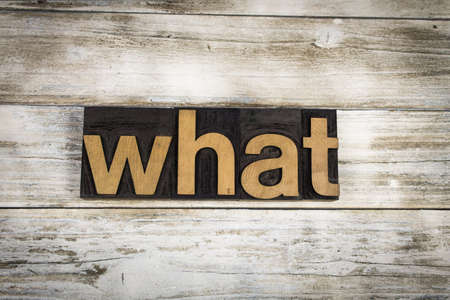 letterpress words: The word what written in wooden letterpress type on a white washed old wooden boards background. Stock Photo