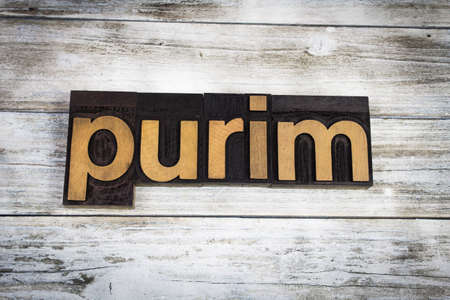 typescript: The word purim written in wooden letterpress type on a white washed old wooden boards background. Stock Photo