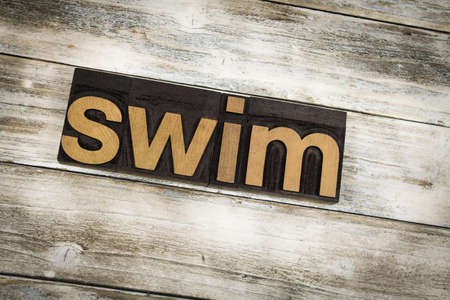 The word swim written in wooden letterpress type on a white washed old wooden boards background.