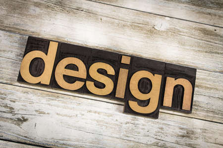 The word design written in wooden letterpress type on a white washed old wooden boards background.