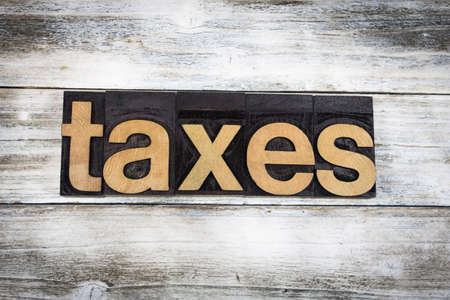 letterpress words: The word taxes written in wooden letterpress type on a white washed old wooden boards background. Stock Photo