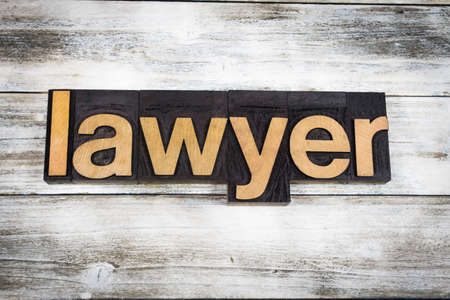 The word lawyer written in wooden letterpress type on a white washed old wooden boards background. Фото со стока