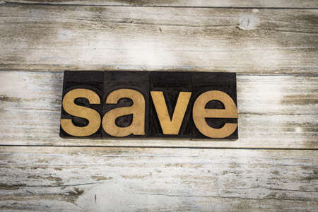 The word save written in wooden letterpress type on a white washed old wooden boards background.