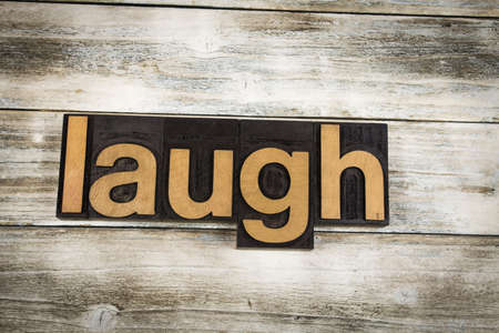 typescript: The word Laugh written in wooden letterpress type on a white washed old wooden boards background. Stock Photo