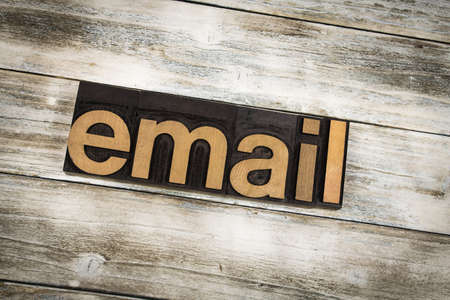 The word email written in wooden letterpress type on a white washed old wooden boards background. Stock Photo