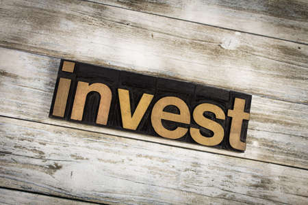 letterpress words: The word invest written in wooden letterpress type on a white washed old wooden boards background.