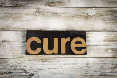 typescript: The word cure written in wooden letterpress type on a white washed old wooden boards background.