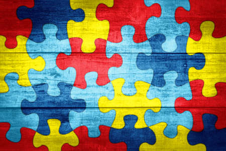 A colorful autism awareness puzzle background with wood texture illustration. Archivio Fotografico