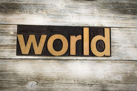 letterpress words: The word world written in wooden letterpress type on a white washed old wooden boards background.