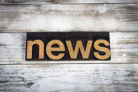 The word news written in wooden letterpress type on a white washed old wooden boards background.