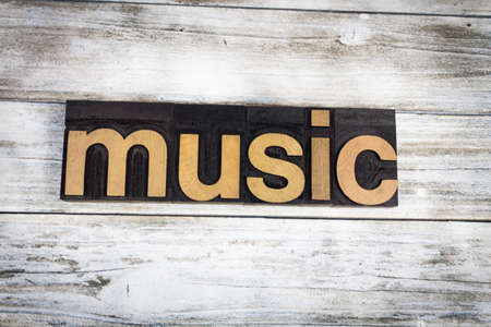 The word music written in wooden letterpress type on a white washed old wooden boards background.