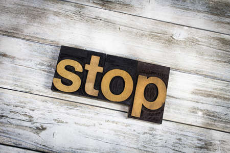 The word stop written in wooden letterpress type on a white washed old wooden boards background.
