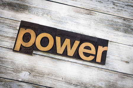 letterpress words: The word power written in wooden letterpress type on a white washed old wooden boards background.