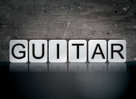 The word Guitar concept and theme written in white tiles on a dark background. Stock Photo