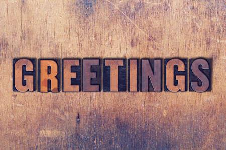 Het concept van woordgroeten en thema in uitstekend houten letterzetseltype op een grungeachtergrond die wordt geschreven.