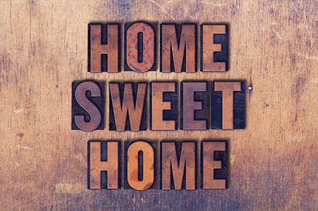 The words Home Sweet Home concept and theme written in vintage wooden letterpress type on a grunge background.