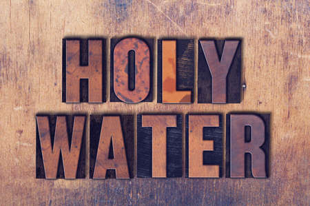 The words Holy Water concept and theme written in vintage wooden letterpress type on a grunge background. Banco de Imagens