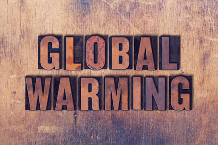 The words Global Warming concept and theme written in vintage wooden letterpress type on a grunge background.