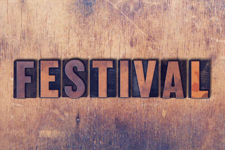 The word Festival concept and theme written in vintage wooden letterpress type on a grunge background.