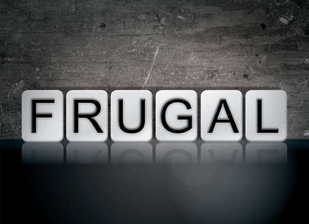 The word Frugal concept and theme written in white tiles on a dark background.
