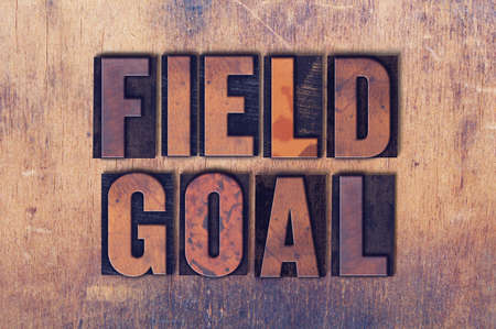 The words Field Goal concept and theme written in vintage wooden letterpress type on a grunge background.