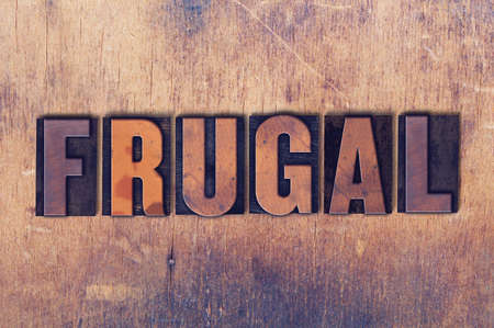 The word Frugal concept and theme written in vintage wooden letterpress type on a grunge background.