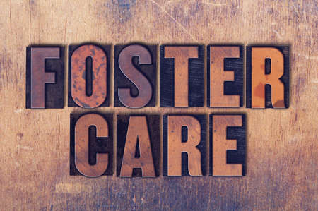 letterpress words: The words Foster Care concept and theme written in vintage wooden letterpress type on a grunge background.