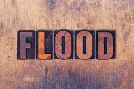 The word Flood concept and theme written in vintage wooden letterpress type on a grunge background.