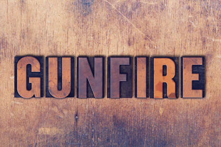 The word Gunfire concept and theme written in vintage wooden letterpress type on a grunge background.
