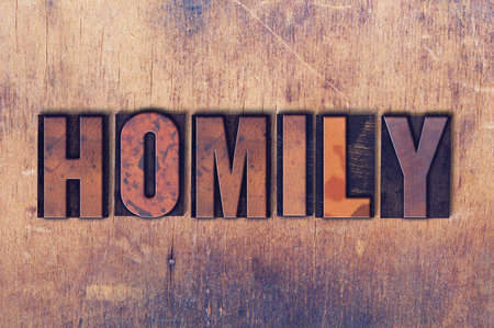 The word Homily concept and theme written in vintage wooden letterpress type on a grunge background.