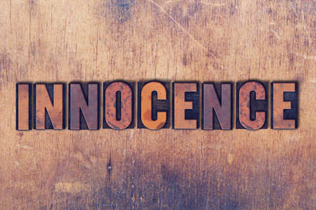 letterpress words: The word Innocence concept and theme written in vintage wooden letterpress type on a grunge background.