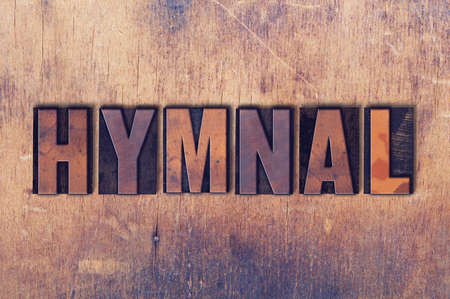 The word Hymnal concept and theme written in vintage wooden letterpress type on a grunge background. Stock Photo - 82358346