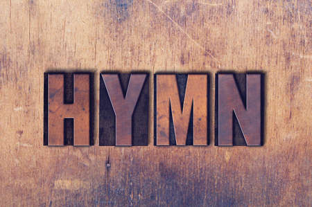 The word Hymn concept and theme written in vintage wooden letterpress type on a grunge background. Stock Photo