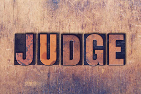 The word Judge concept and theme written in vintage wooden letterpress type on a grunge background.