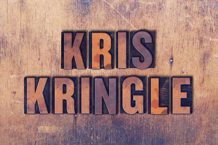 kris kringle: The name Kris Kringle concept and theme written in vintage wooden letterpress type on a grunge background.