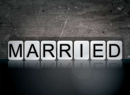 The word Married concept and theme written in white tiles on a dark background. Banco de Imagens