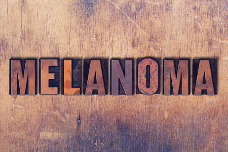 The word Melanoma concept and theme written in vintage wooden letterpress type on a grunge background.