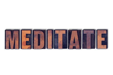 The word Meditate concept and theme written in vintage wooden letterpress type on a white background. Imagens