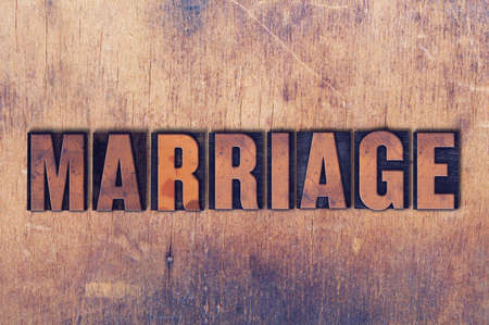 The word Marriage concept and theme written in vintage wooden letterpress type on a grunge background.