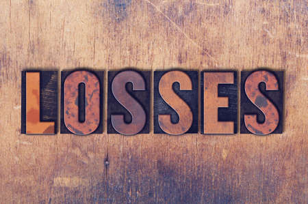 The word Losses concept and theme written in vintage wooden letterpress type on a grunge background. Banco de Imagens