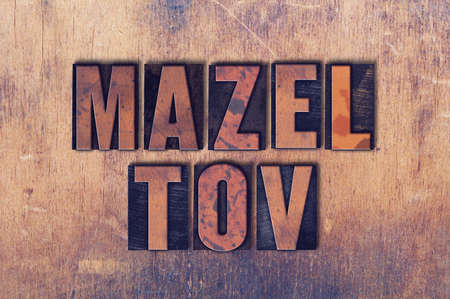 The words Mazel Tov concept and theme written in vintage wooden letterpress type on a grunge background. Banco de Imagens