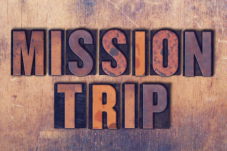 The words Mission Trip concept and theme written in vintage wooden letterpress type on a grunge background.