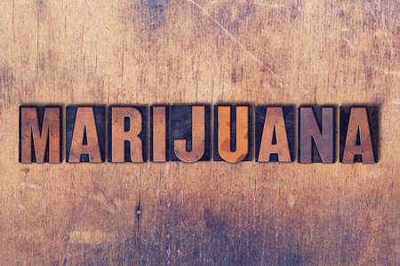 The word Marijuana concept and theme written in vintage wooden letterpress type on a grunge background.