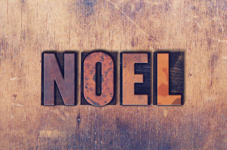 The word Noel concept and theme written in vintage wooden letterpress type on a grunge background.