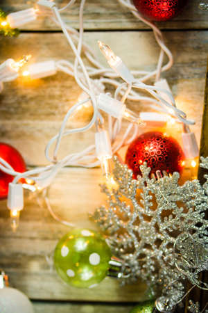 A set of Christmas holiday lights and ornaments on a white washed vintage wood background.